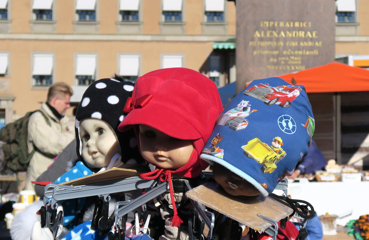 Oheistuotteita torin puolella. Taustalla Keisarinnan kivi -muistomerkin jalusta. Nikolai I ja keisarinna Aleksandra Fjodorovna vierailivat Helsingissä ja astuivat maihinKauppatorilla 1833.
